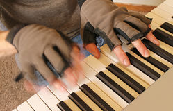 A pianist wears fingerless gloves while playing to keep his hands warm. A pianist fights the chill of winter by playing with fingerless gloves. One hand strikes Stock Images