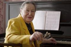 Pianista affascinante anziano di signora nella disposizione dei posti a sedere del rivestimento giallo al piano con i vetri in su Immagine Stock
