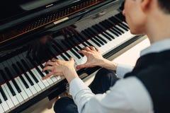 Pianista bawić się muzykę na uroczystym pianinie fotografia stock