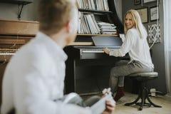 Pianista joven acompañado por un guitarrista masculino Foto de archivo