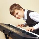 Pianista joven del principiante en el traje que juega el piano electrónico Fotografía de archivo libre de regalías