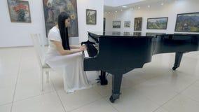 Pianista musicale che gioca pianoforte a coda classico in un centro della sala da concerto colpo dello steadycam archivi video