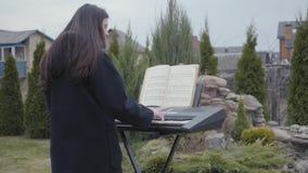 Pianista profissional para jogar a música clássica do piano no sintetizador no quintal Série real dos povos vídeos de arquivo