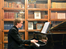 Pianista que juega en piano de cola negro Imagenes de archivo