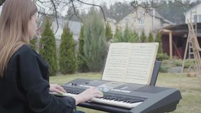 Pianiste mignon professionnel jouer la musique classique de piano sur le synthétiseur dans l'arrière-cour Vraie série de personne banque de vidéos