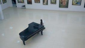 Pianiste musical jouant le piano à queue classique à un centre de salle de concert tir de steadycam clips vidéos