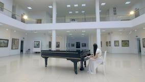 Pianiste musical jouant le piano à queue classique à un centre de salle de concert tir de steadycam banque de vidéos