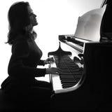 Pianisten spelar flygeln Arkivbild