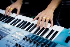 Pianisthand mit Ring auf dem Klavier Stockfoto