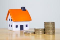 Piankowy dom siedzi za stertą pieniądze - wartości nieruchomości pojęcie Zdjęcie Stock