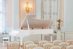 Piano à queue blanc sur la salle de concert Photographie stock libre de droits