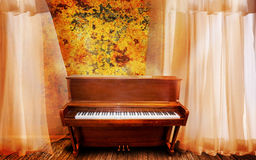 Piano. An upright wooden piano on a wooden stage with light breezy curtains royalty free stock photo