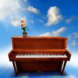 Piano. A wooden upright piano with a cloudy background and a flower royalty free stock image