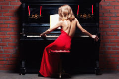Piano. Beautiful young woman playing the piano royalty free stock images