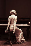 Piano. Beautiful young attractive woman in cocktail dress and piano stock photo