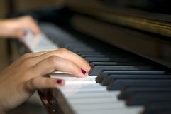 Piano. Young girl hands playing in piano keyboard Stock Images
