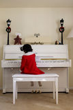 Piano. A child playing a white piano wearing a red dress Royalty Free Stock Photography