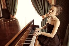 Piano. Beautiful woman playing piano in a luxury interior royalty free stock image
