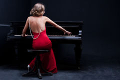 Piano. Beautiful young attractive woman in cocktail dress and piano Royalty Free Stock Photo