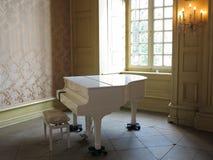 Piano blanco en el ambiente con clase Imagen de archivo libre de regalías
