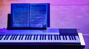 Piano in blue violet color. Notes of classical music stock images