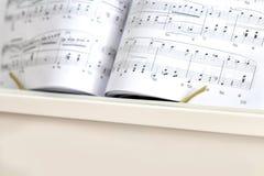 Piano branco com notas do piano Fim acima fotografia de stock royalty free