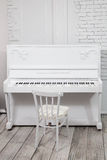Piano branco com tamborete branco na frente de uma parede de tijolo branca Fotografia de Stock