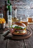Piano burger with bacon and cutlet with cheese, tomato, greens. stock image