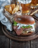 Piano burger with bacon and cutlet with cheese, tomato, greens. royalty free stock photos