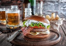 Piano burger with bacon and cutlet with cheese, tomato, greens. Served with fries and beer on a wooden table royalty free stock image
