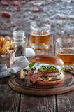 Piano burger with bacon and cutlet with cheese, tomato, greens. royalty free stock photography