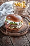 Piano burger with bacon and cutlet with cheese, tomato, greens. stock photography