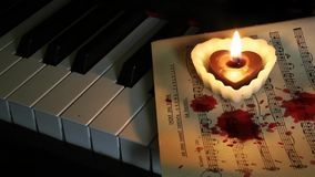 Piano Candle and Blood Drops on Music Sheet. Piano Heart Shape Candle and Blood Drops on Music Sheet video stock video