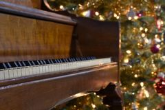 A piano with a Christmas tree in the background stock photo