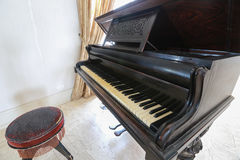 Piano classic with wooden chair in the room. Royalty Free Stock Photo