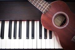 Piano com uquelele Fundo da arte e da música Vista superior com vinheta escura foto de stock royalty free