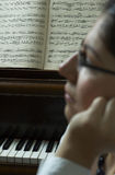 Piano Composition. Pensive portrait of a piano teacher sitting in profile in front of a piano, with music open on the piano stand.  Teacher seated to far right Stock Images