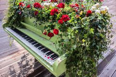 Piano covered with flowers outdoor. Music concept. Piano covered with flowers stands outdoor on a wooden flooring. Original landscape design in city street stock images