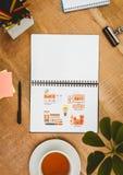 Piano d'appoggio con un taccuino con i grafici di web Fotografia Stock