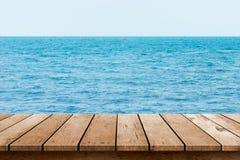 Piano d'appoggio di legno con il fondo del mare fotografie stock