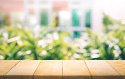 Piano d'appoggio di legno su sfuocatura della finestra con il fondo del fiore del giardino fotografia stock libera da diritti