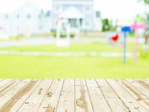 Piano d'appoggio di legno sugli ambiti di provenienza confusi del tappeto erboso domestico Fotografia Stock