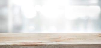 Piano d'appoggio di legno sul fondo della costruzione della parete della finestra di vetro della sfuocatura Immagine Stock Libera da Diritti
