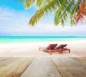 Piano d'appoggio di legno sul fondo della spiaggia della sfuocatura con le sedie di spiaggia Immagine Stock
