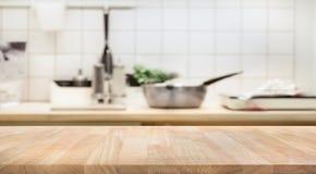 Piano d'appoggio di legno sul fondo della stanza della cucina della sfuocatura fotografie stock libere da diritti