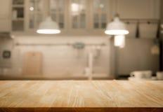 Piano d'appoggio di legno sul fondo della stanza della cucina della sfuocatura immagini stock