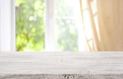 Piano d'appoggio di legno sul fondo vago della finestra per l'esposizione del prodotto fotografia stock