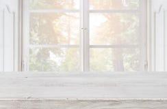 Piano d'appoggio di legno vuoto su fondo vago della finestra d'annata Immagini Stock