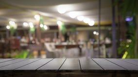 Piano d'appoggio e sfuocatura di legno vuoti del fuoco selettivo del fondo del pub o del ristorante di notte immagine stock
