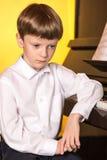 Piano de garçon Pianiste avec l'instrument de musique classique de piano à queue Images stock